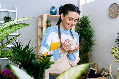 Young woman working in a gardening laboratory or plant shop - p300m2275446 von Giorgio Fochesato