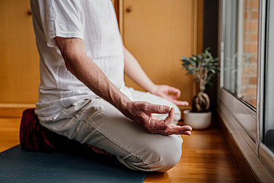 Senior man gesturing OK sign while doing yoga at home - p300m2281373 by VITTA GALLERY