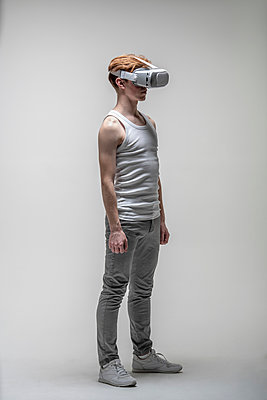 Young man using virtual reality simulator glasses - p301m2018406 by Vasily Pindyurin