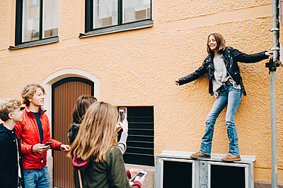 Female photographing girl while standing with friends at city - p426m1555866 by Maskot