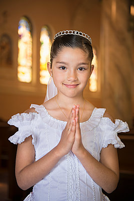 Hispanic girl with hands clasped in church - p555m1478494 by Sollina Images