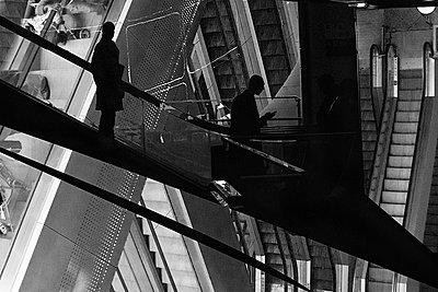 People riding escalator, black and white image - p6751795 by Bruno Veillard