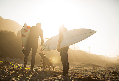 Surfers with dog in sunlight holding surfboards on beach, Malibu, California, USA - p924m1422760 by Raphye Alexius