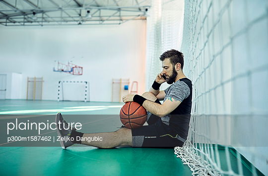 Man with basketball using smartphone, indoor - p300m1587462 von Zeljko Dangubic