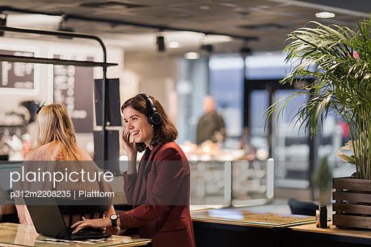 Woman wearing headset working in office - p312m2208235 by Plattform