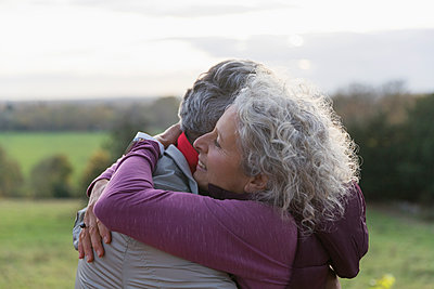 Affectionate senior couple hugging in field - p1023m1583906 by Tom Merton