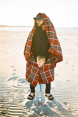 A father warming up his son with a blanket on a windy beach - p1166m2200133 by Cavan Images