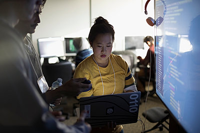 Hacker team coding at laptop and computer monitor at hackathon in dark office - p1192m1202097 by Hero Images