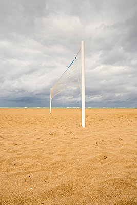 Volleyball net on a sandy beach with cloudy sky above - p1302m1559614 by Richard Nixon