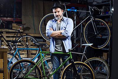 Portrait of confident man in bicycle workshop - p300m1562674 by Josep Suria