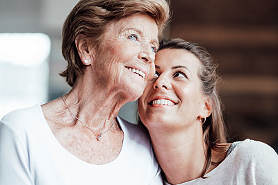Smiling woman looking at contemplating grandmother at home - p300m2274968 by Gustafsson