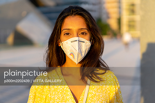 Confident young woman wearing face mask in city - p300m2202439 by VITTA GALLERY