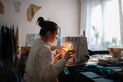 Young seamstress working at home - p1166m2216786 by Cavan Images