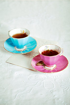 Tea Cups with Letter on Tablecloth - p1248m2125837 by miguel sobreira