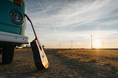 Guitar leaning against camper van in rural landscape with wind turbines at sunset - p300m2058784 von Gustafsson