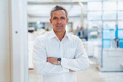 Portrait of a confident businessman in a factory - p300m2159998 by Daniel Ingold