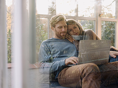 Man with wife using laptop in sunroom at home - p300m2167221 by Kniel Synnatzschke