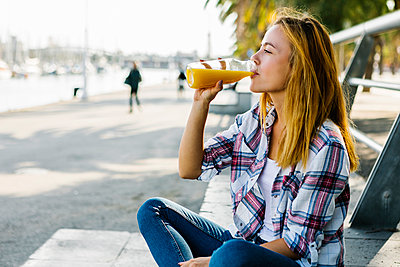 Young woman drinking juice while sitting on footpath in city - p300m2227365 by Xavier Lorenzo