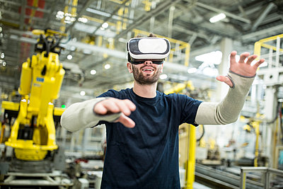 Man wearing VR glasses in modern factory - p300m2246019 by Westend61