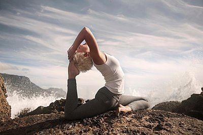 Woman practising yoga by ocean, Cape Town, South Africa - p429m1054427f by Seb Oliver