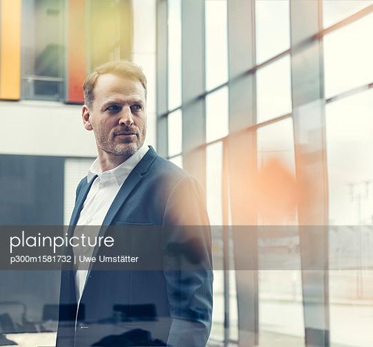 Confident businessman looking out of window - p300m1581732 von Uwe Umstätter