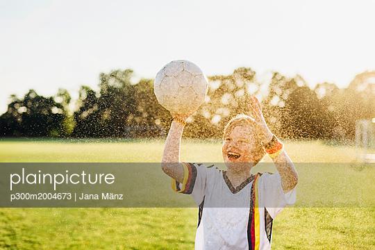 Boy wearing German soccer shirt screaming for joy, standing in water splashes - p300m2004673 von Jana Mänz
