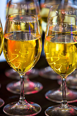 A collection of wine glasses full of richly coloured white wine and highlighting the reflections of the ligfhst in the room above. - p1057m1553047 by Stephen Shepherd