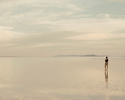 A woman standing on the flooded Bonneville Salt Flats at dusk. Reflections in the shallow water. - p1100m875905f by Paul Edmondson