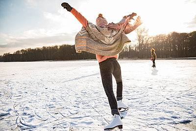 Rear view of woman with ice skates on frozen lake - p300m1460016 by Mareen Fischinger
