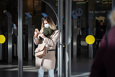 Woman with face mask, using smartphone at subway station - p300m2170832 by Vasily Pindyurin