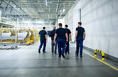 Colleagues having a break and walking in a modern car factory - p300m2245984 by Westend61