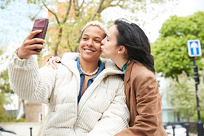 Smiling woman taking selfie with girlfriend kissing on cheek - p300m2290722 by Pete Muller