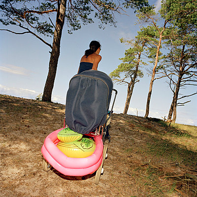 Woman and a perambulator with toys on Öland Sweden. - p31216709f by Ulf Huett Nilsson