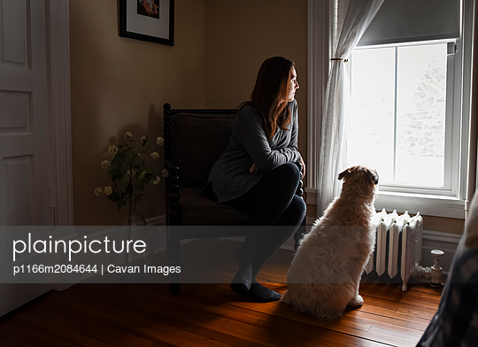 Woman sitting in chair in dark room looking out window with dog - p1166m2084644 by Cavan Images