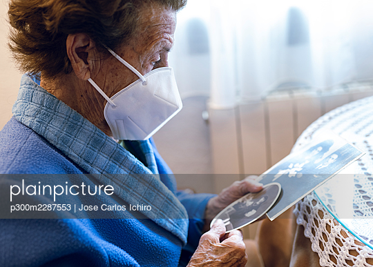 Senior woman wearing protective face mask watching old photograph at home - p300m2287553 by Jose Carlos Ichiro