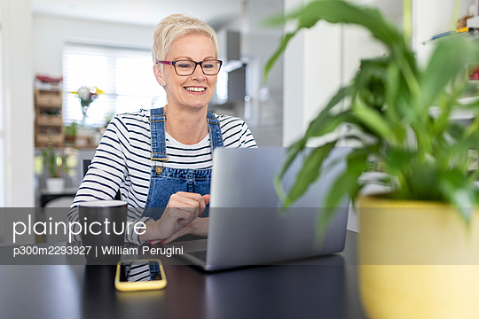 Smiling businesswoman looking at laptop on desk in home office - p300m2293927 by William Perugini