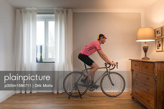 Mann auf Rennrad in seiner Wohnung - p305m1586711 von Dirk Morla