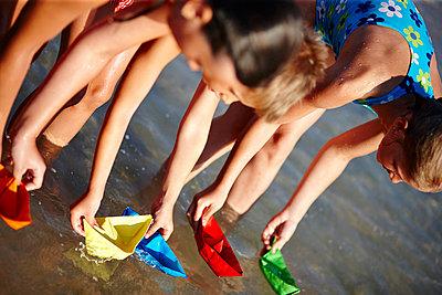 Kinder am Strand spielen mit Booten aus Papier - p1026m834448 by Secen-Steets