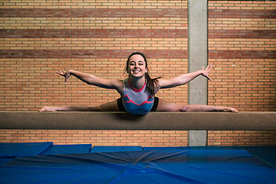 Full length portrait of female gymnast with legs apart and arms outstretched exercising on balance beam against wall at gym - p1166m1576456 by Cavan Images