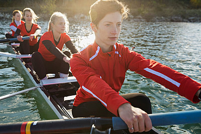 Rowing team in scull on river - p1192m1016575f by Hero Images