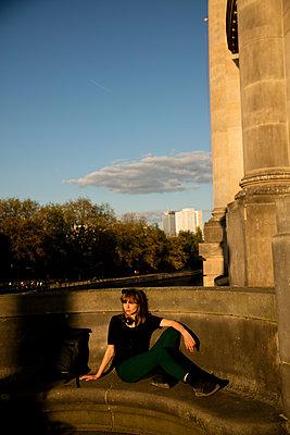 Junge Frau in der Abendsonne auf der Steinbank - p1212m1137047 von harry + lidy