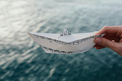 Hand at the water holding paper boat made of music sheet - p300m1166798 by Boy photography
