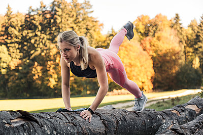 Young woman doing pushups on tree trunk during workout in nature - p300m2084070 by Sebastian Dorn