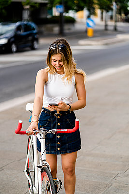 Smiling young woman with racing cycle looking at cell phone - p300m2119839 by Giorgio Fochesato
