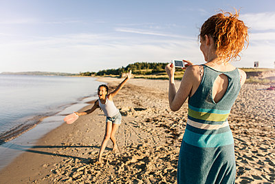 Rear view of woman photographing playful daughter standing on shore at beach against sky - p426m1588245 by Kentaroo Tryman