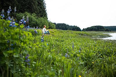 Single woman on the lakefront, Alaska, USA - p741m2168717 by Christof Mattes