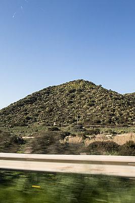 Blick aus dem Autofenster auf einen Hügel - p930m1221997 von Phillip Gätz