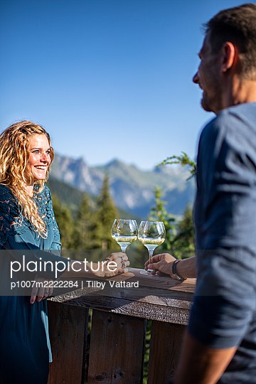 Young couple takes a glass of wine on the terrace - p1007m2222284 by Tilby Vattard