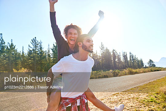 Portrait carefree young couple piggybacking at sunny remote roadside - p1023m2212886 by Trevor Adeline