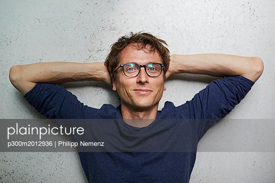 Portrait of smiling man with hands behind head wearing glasses - p300m2012936 von Philipp Nemenz